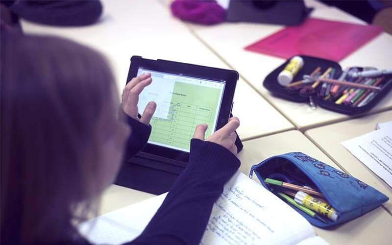 menina utilizando a tablet em sala de aula
