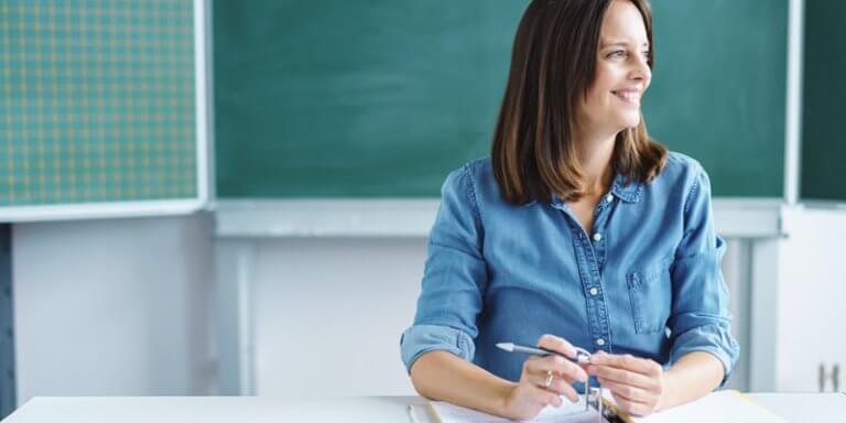 Mulher sentada na sala de aula, segurando uma caneta e olhando para o lado