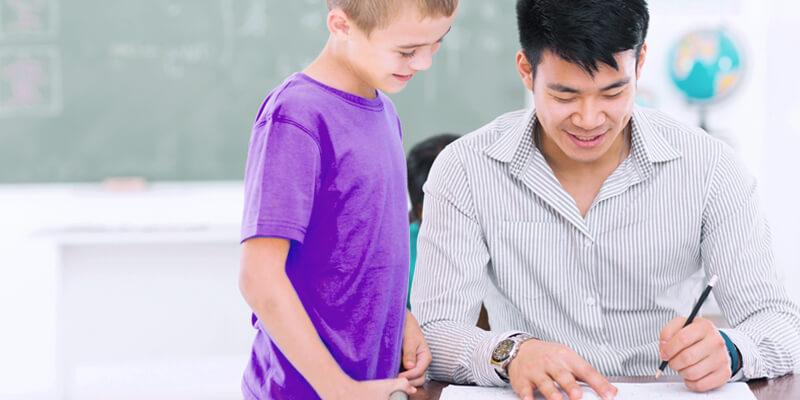 aluno ao lado do professor que está sentado em sua carteira, ajudando na lição