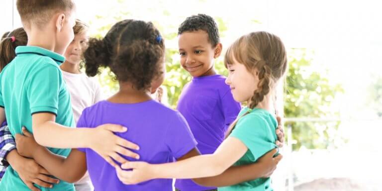 crianças em circula se abraçando e sorrindo