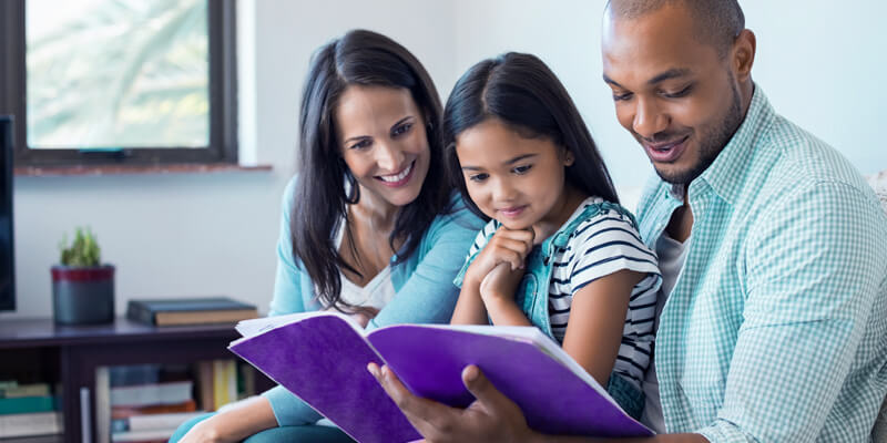 pai e mãe lendo com a filha