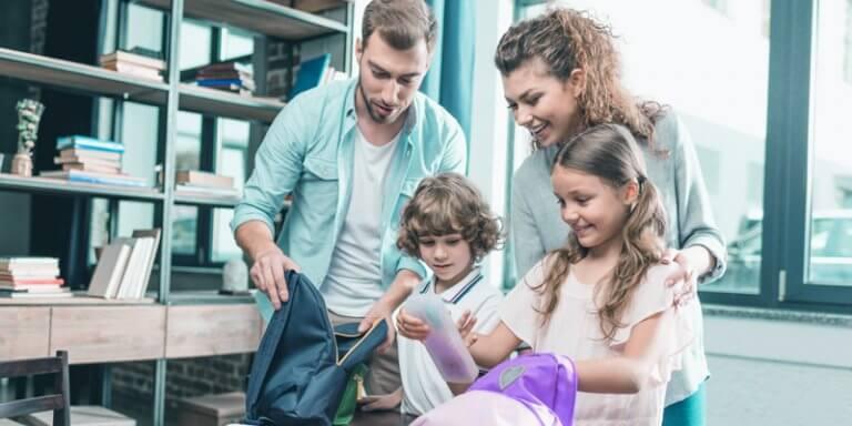 família formada por pai, mãe e dois filhos (menino e menina), arrumando a mochila que está sobre uma mesa. Atrás deles existe uma estante com livros.