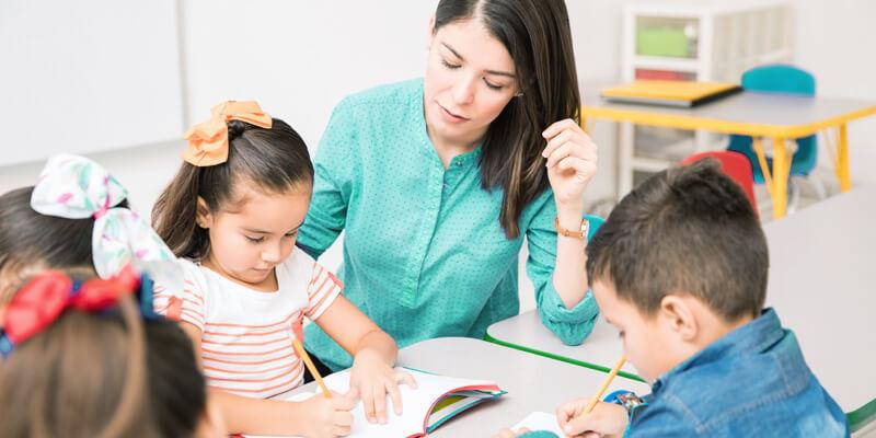 professora em sala de aula, ao lado de duas crianças que estão com seus cadernos
