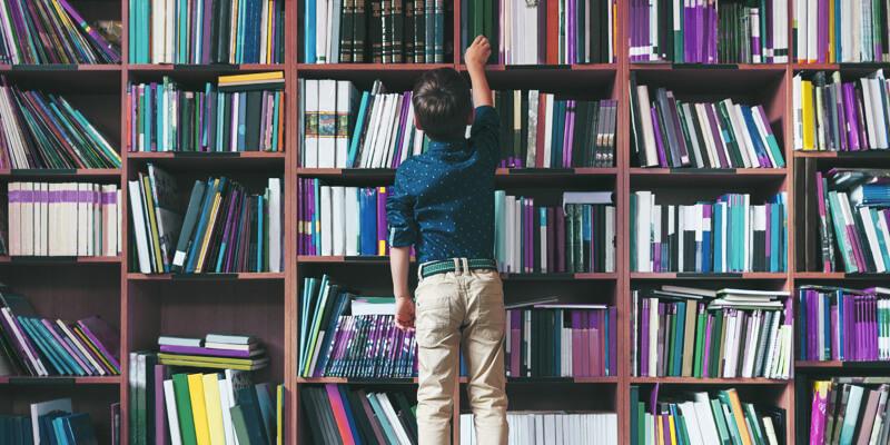 criança de costas na biblioteca escolhendo um livro