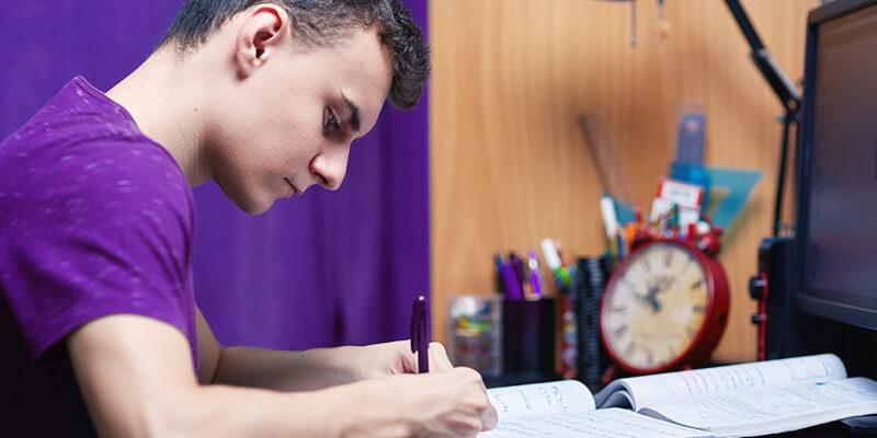 aluno estudando em casa e sob a mesa há cadernos, canetas, computador e livros