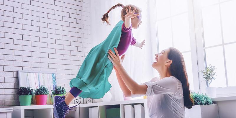 Mãe levantando sua filha, brincando de faz de conta de super-herói na cama