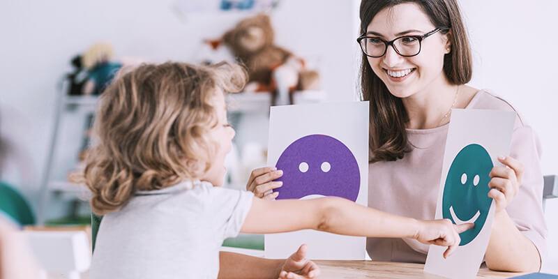 professora segurando placas de feliz e triste e criança escolhendo a opção da carinha feliz