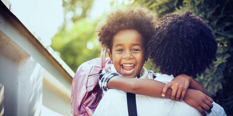 criança nos braços da mãe indo para a escola
