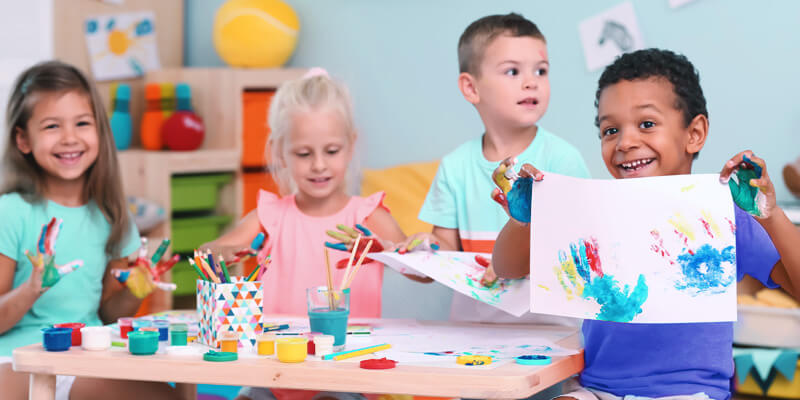 quatro crianças brincando de desenhar em sala de aula. Uma delas está com segurando o seu desenho