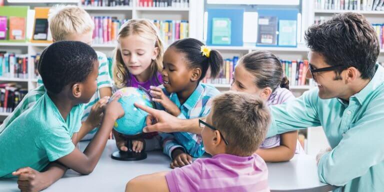 crianças e professor em sala de aula ao redor de um globo terrestre