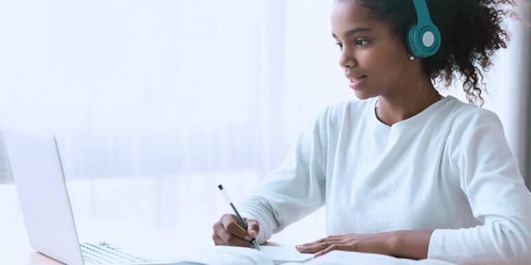 Jovem com fone de ouvido estudando com caderno e computador na mesa.