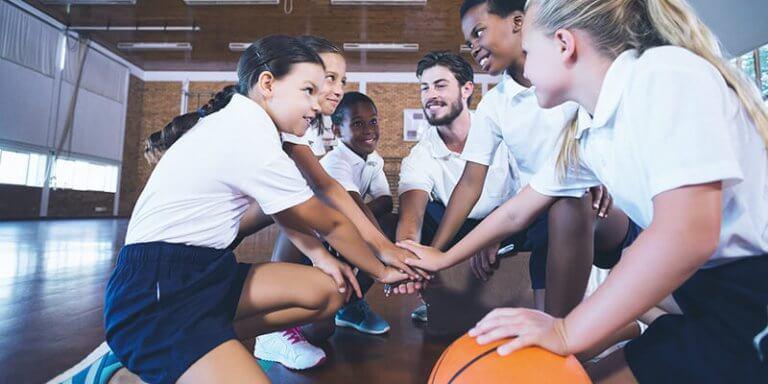 plano de aula de educação física: crianças e professor agachados e de mão dadas para jogar basquete