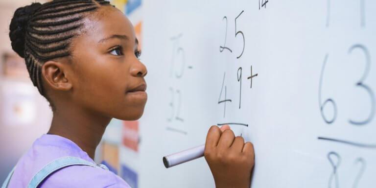 racismo na escola: criança negra resolvendo um exercício na lousa da sala de aula