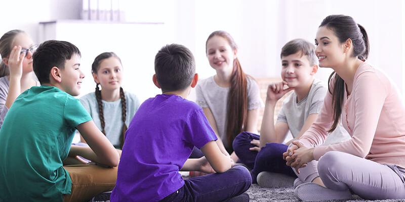 crianças com a professora sentados em circulo e conversando