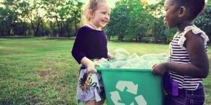 sustentabilidade nas escolas: duas crianças segurando um cesto de lixo reciclável