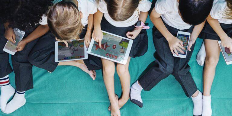 crianças sentadas e brincando em celulares e tablets