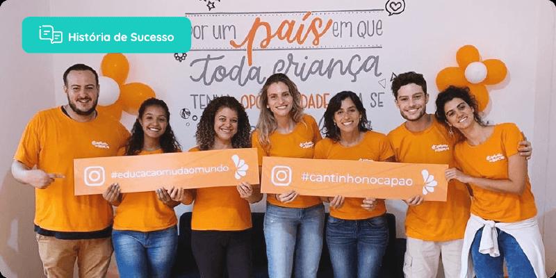 Equipe da escola, todos de camisa laranja, segurando uma placa com hashtag educação muda o mundo e a na outra placa o instagram da escola.