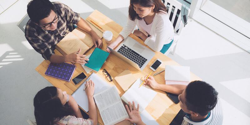 Conselhos de classe: pessoas ao redor de uma mesa, conversando.