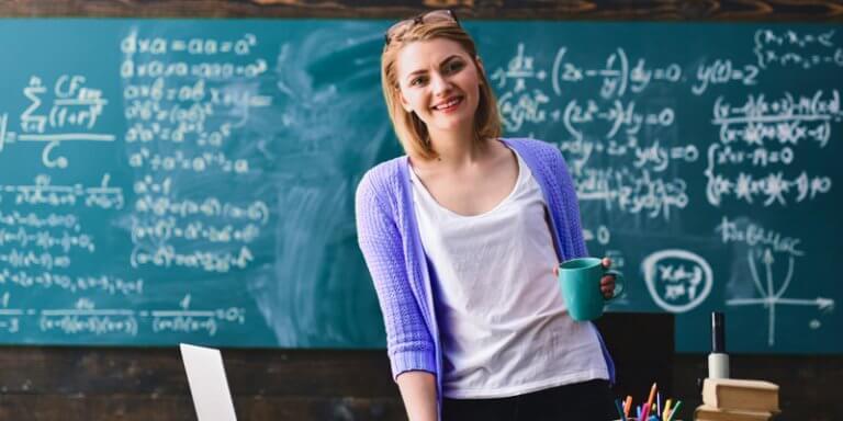 Professora em pé, na frente do quadro negro, segurando uma caneca