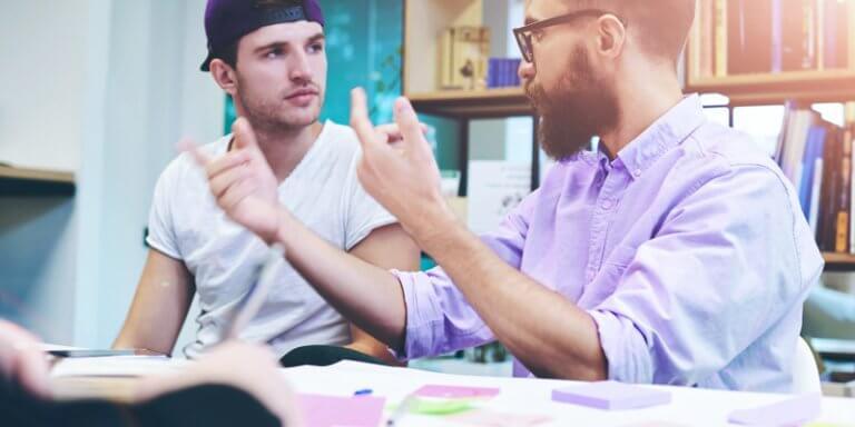 Inteligência emocional dos alunos no Enem: Aluno e professor sentados e conversando. Há uma mesa frente a eles.