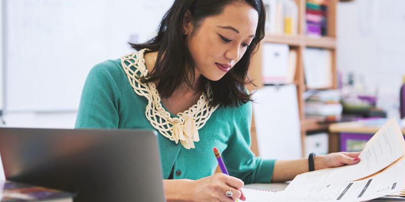 Tempo do professor: Mulher em uma mesa com computado. Atrás dela há diversos livros, a mesma está assinando papeis.