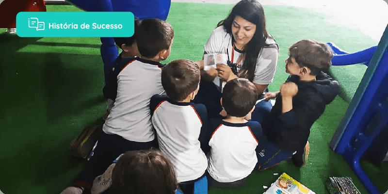 história de sucesso: professora agachada, brincando com os alunos no pátio da escola