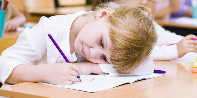 dificuldade de aprendizagem: criança loira escrevendo e com a cabeça deitada na carteira da sala de aula