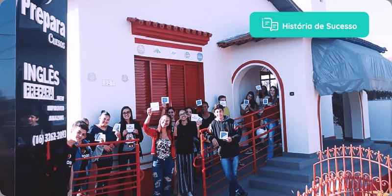 história de sucesso: alunos em pé, em frente a escola, segurando plaquinhas com o logo da Agenda Edu