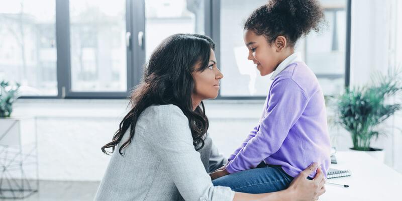 disciplina positiva: mulher conversando com a criança que está sentada em cima de uma pesa