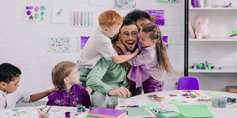 Professor da Educação Infantil sorrindo e sendo abraçado por alunos na sala de aula