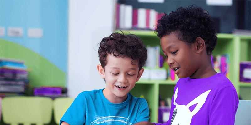 Dois alunos estudando juntos na sala de aula com agrupamentos produtivos