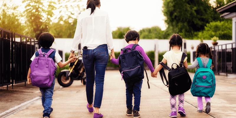 Monitor escolar acompanhando crianças na entrada da escola