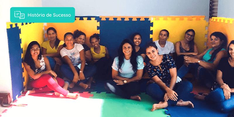 Colaboradores da escola Baby Camp sentados lado a lado em uma sala e sorrindo para a foto