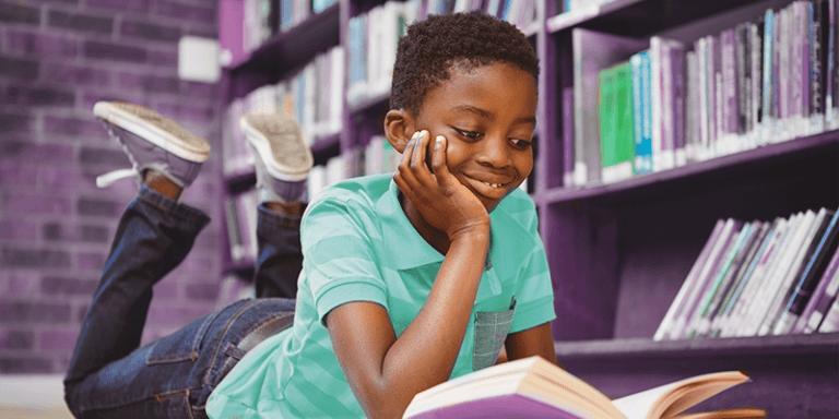 Menino deitado de barriga para baixo no chão da biblioteca da escola, lendo um livro com a mão no queixo e sorrindo