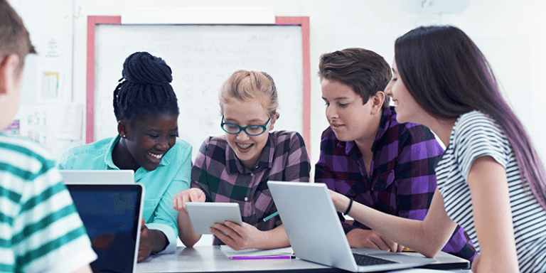 Crianças sentadas ao redor de uma mesa na escola sorrindo e estudando juntas com notebooks e tablets