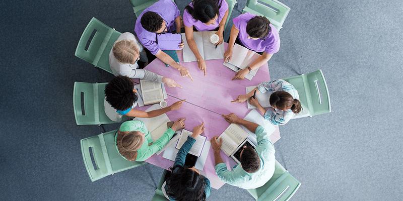Visão de cima de vários alunos sentados em volta de uma mesa com livros, gesticulando e estudando juntos
