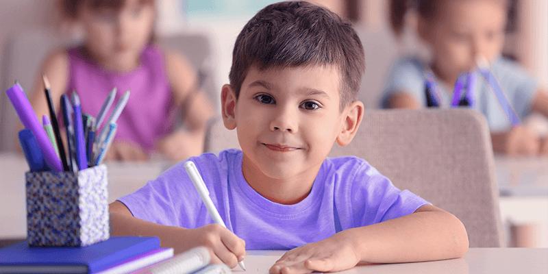 Menino com pequeno sorriso sentado na mesa na escola e escrevendo com um lápis