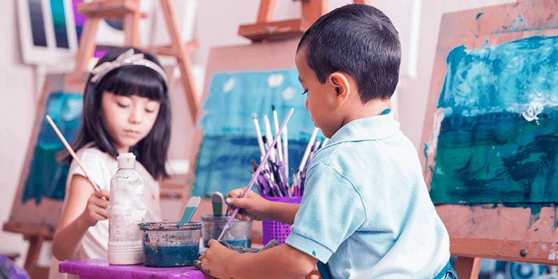 Duas crianças com pincéis escolhendo tinta em uma sala de artes com quadros. Imagem representa um dos tipos de escola fora da linha tradicional