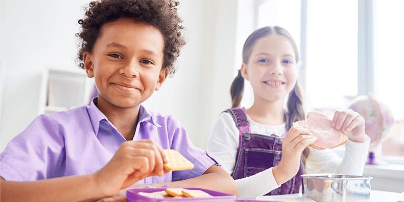 Duas crianças sentadas e comendo lanches com alimentação infantil saudável