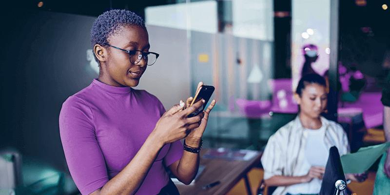 Professora utilizando celular com aplicativos para escolas na sala de aula com alunos ao fundo estudando
