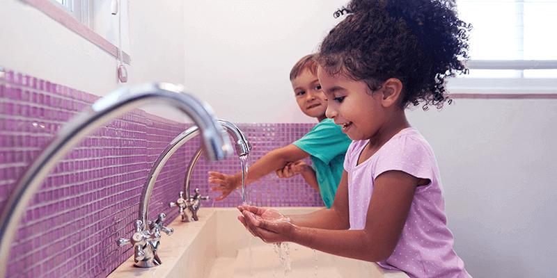Crianças se prevenindo contra o coronavírus lavando as mãos no banheiro da escola