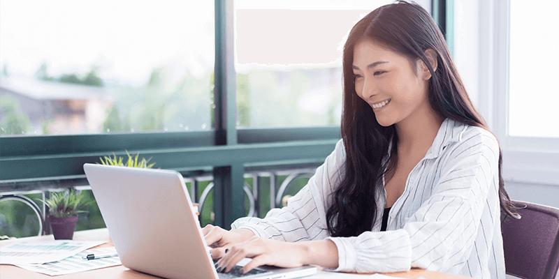 Mulher sentada em mesa olhando para o notebook, fazendo seu plano de ação escolar e sorrindo. Ao fundo, uma janela mostrando a cidade