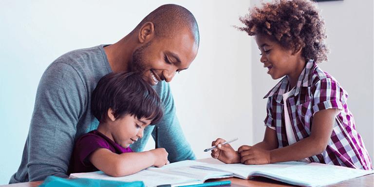 Pai e dois filhos estudando e cumprindo da rotina escolar em casa, sentados na mesa da sala com livros