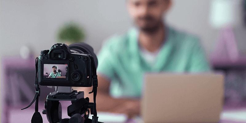 Professor gravando videoaulas em casa com câmera, sentado em uma mesa com o notebook