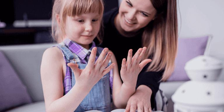 Mãe ensinando filha sobre o coronavírus e as formas de prevenção