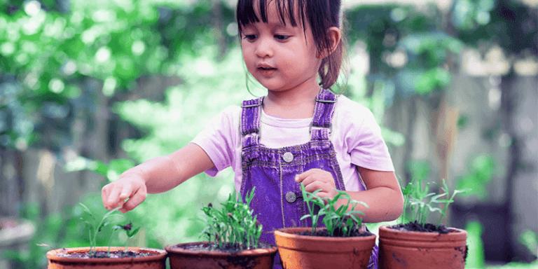 Menina no jardim de casa limpando quatro vasos de plantas para prevenção contra a dengue