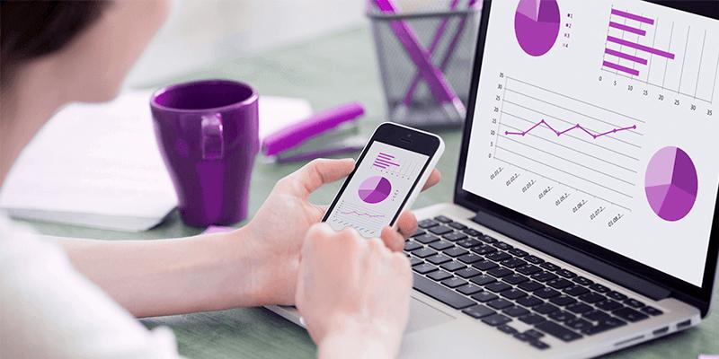Mulher com celular na mão e notebook em mesa de trabalhando conferindo gráficos e dados sobre gestão escolar