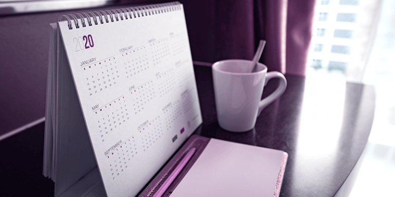 Calendário de 2020 sobre mesa ao lado de xícara de café, representando o ano letivo escolar