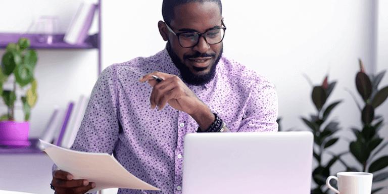 Professor planejando plano de aula online em casa, sentado na mesa com notebook e papel na mão