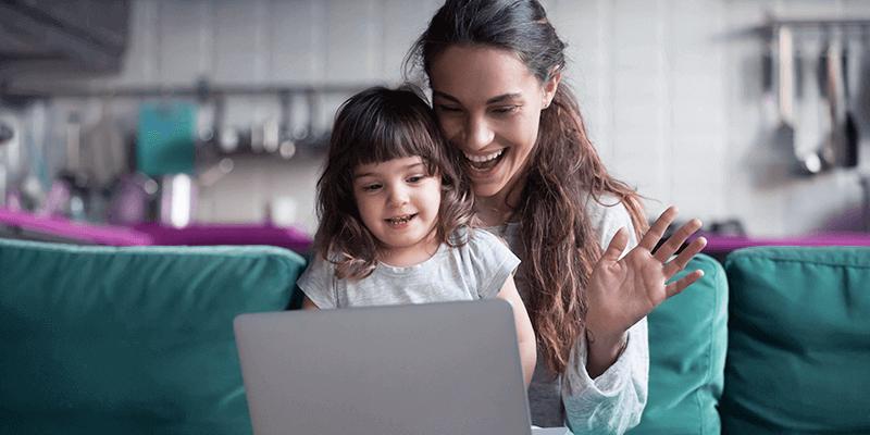 Mãe e filha fazendo videochamada na sala de casa e mantendo a comunicação entre escola e família